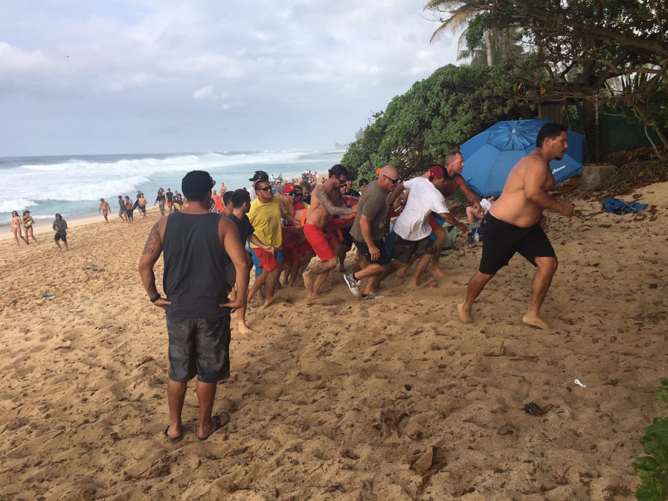 Lifeguards, paramedics, and locals help carry Kalani Chapman to a waiting ambulance.